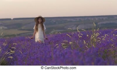 Girl with curls walks through the flowering field of lavender on the sunset