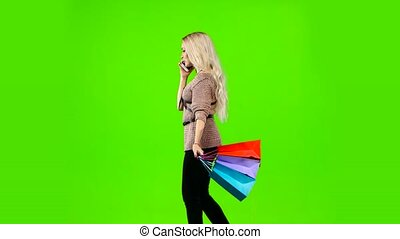 Girl with curly hair with bags in their hands on the phone. Green screen. Side view