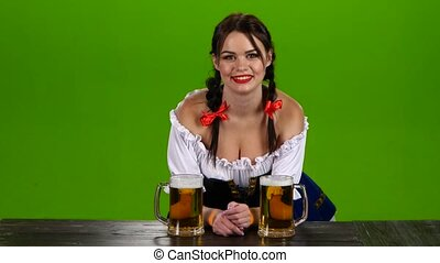 Girl with dark hair and flirting at Oktoberfest offers beer....