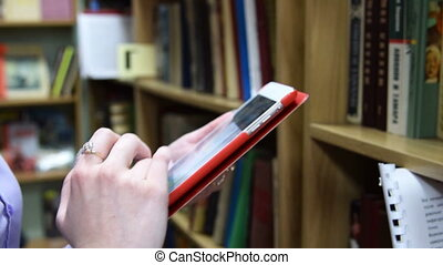 Girl with digital tablet in the library