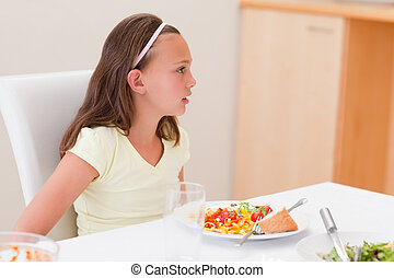 Girl with dinner at the table