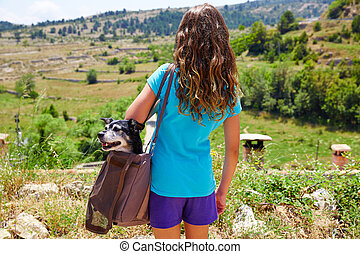 Girl with dog in a bag rear view looking mountains