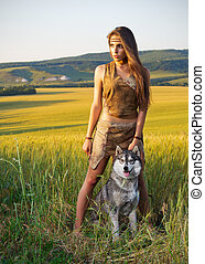 Girl with dog in a wheat field