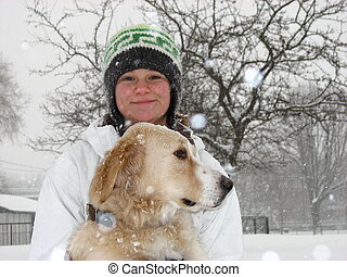 Girl with dog in snow. - A girl standing in the snow with...