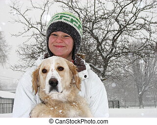 Girl with dog in snow - A girl standing in the snow with her...
