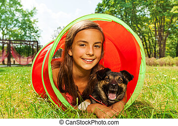 Girl with dog play in playground tube
