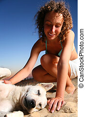 Girl with dog sits on sand