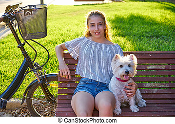 Girl with dog sitting in a park bench