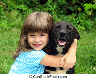 Girl with dog - Little girl, smiling, with black dog in an...