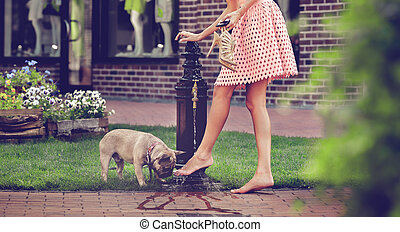 Girl with dog washing legs in the well