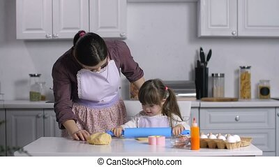 Girl with down syndrome kneading dough in kitchen - Cheerful...