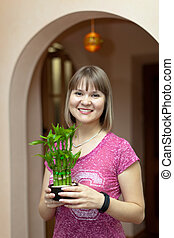Girl with dracaena in the pot