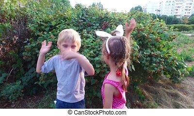 Girl with ears and glasses and boy with white hair standing near the bush and waving their hands.
