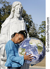 Girl with Earth and Jesus Statue - A girl holding the Earth...
