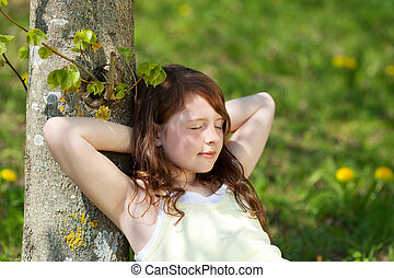 Girl With Eyes Closed Leaning On Tree Trunk In Park - Young...