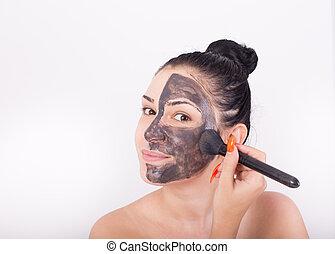 Girl with facial mask - Young pretty woman applying facial...