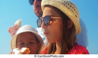 girl with family eating sandwich on summer beach - leisure ...