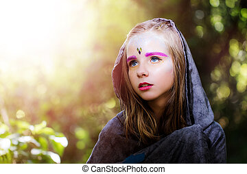 Girl with fantasy make up in woods.