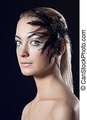 girl with feathered accessory, she looks in to the lens