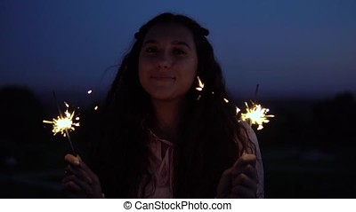 Girl with fireworks in hands on a background of a night city. slow motion.