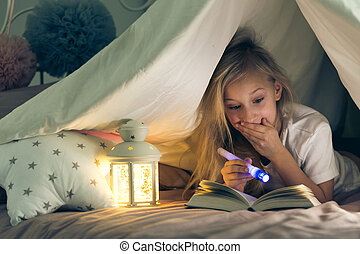 Girl with flashlight reading book