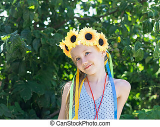 Girl with flower decoration on the head looks.