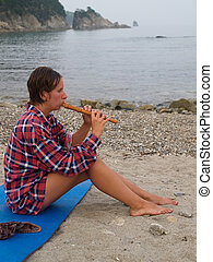 girl with flute on the beach