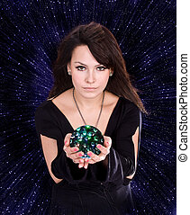 Girl with fortune telling ball against star sky. ...