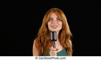 Girl with freckles sings in a retro microphone. Black...