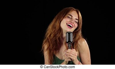 Girl with freckles sings in a retro microphone. Black background. Slow motion