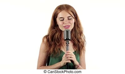 Girl with freckles sings in a retro microphone. White background. Slow motion