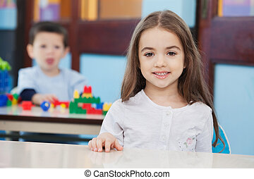 Girl With Friend In Background At Preschool