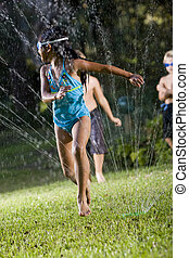 Girl with friends playing in lawn sprinkler