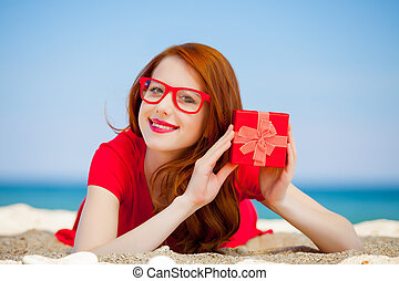girl with gift box on the beach