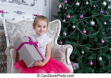 Girl with gift-box under Christmas tree