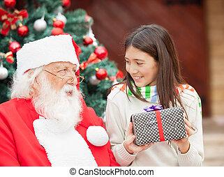 Girl With Gift Looking At Santa Claus
