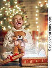 girl with gift near Christmas tree