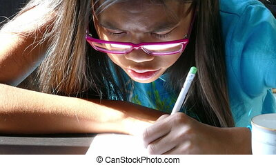 Girl With Glasses Draws Picture - A cute 13 year old Asian...