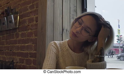 Girl with glasses talking with a friend in a cafe