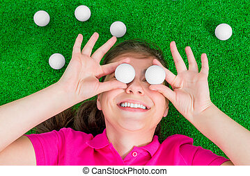 girl with golf balls before his eyes laughing lying on the grass