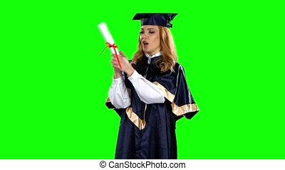Girl with graduation gown and diploma. Green screen - Girl...