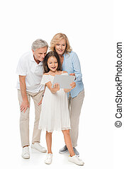 girl with grandparents looking at tablet