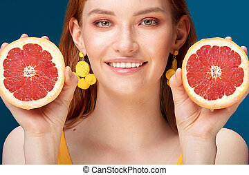 Girl with grapefruit on blue background.