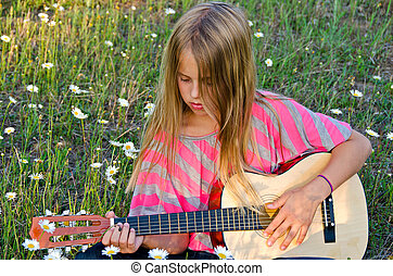 girl with guitar in wildflowers