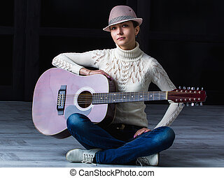 girl with guitar sitting on the floor