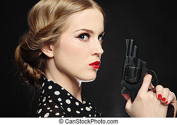 Girl with gun - Portrait of beautiful young angry blond...