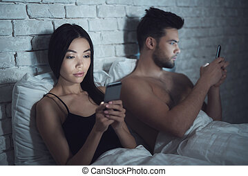 Girl with guy lies in a dark room in bed. They are looking...