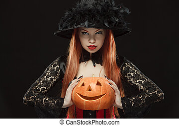Girl with Halloween pumpkin on black background