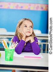 Girl With Hand On Chin Sitting At Desk In Kindergarten