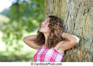 Girl With Hands Behind Head Leaning On Tree Trunk